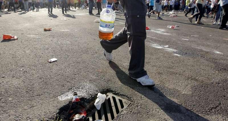 En la imagen, un joven lleva una garrafa de cerveza improvisada. EFE/Kai Forsterling/Archivo