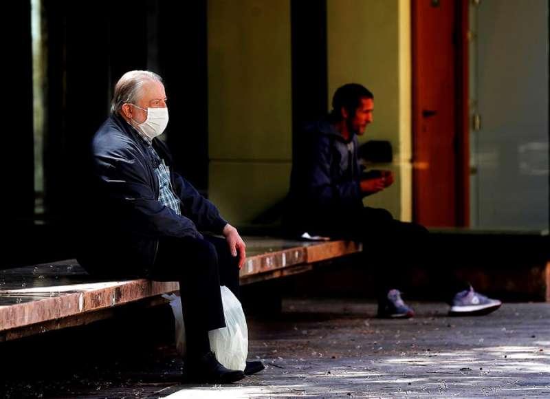 Un hombre descansa sentado en un banco tras realizar la compra en una plaza del barrio del Carmen de Valencia en el cuadragésimo quinto día de confinamiento. EFE