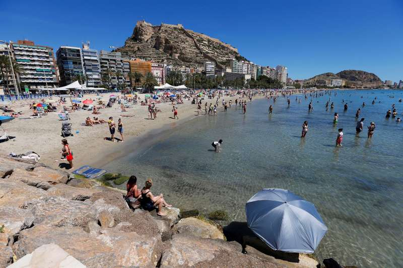 Bañistas disfrutan de un día de sol en la playa del Postiguet en Alicante.