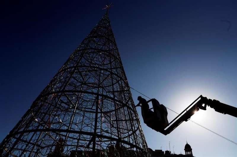 Un operario trabaja en el montaje del árbol de navidad de la plaza del Ayuntamiento de Valencia. EFE