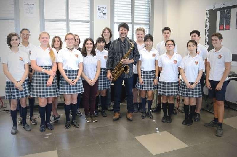 El saxofonista Josvi Muñoz con un grupo de alumnos de música de Caxton College. epda