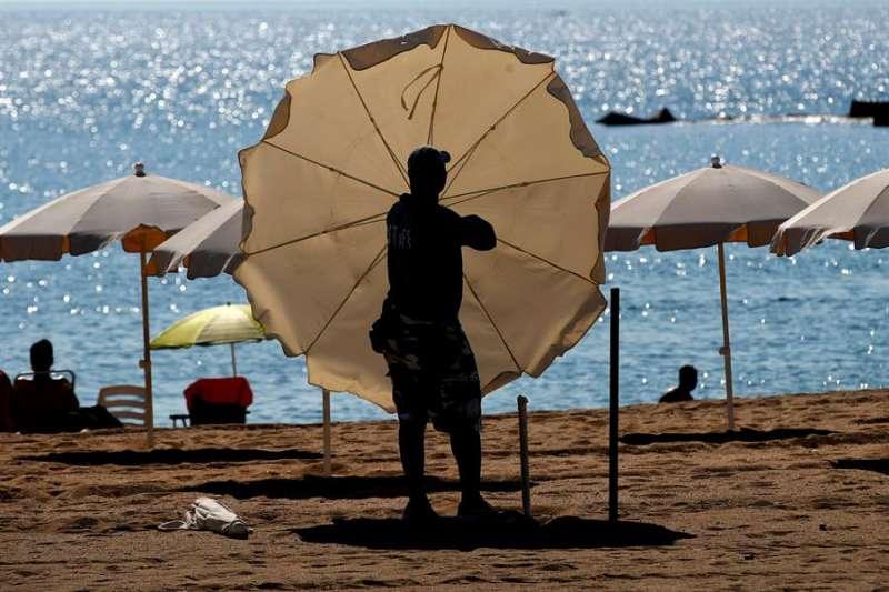 Un trabajador instala las sombrillas y hamacas en una playa. EFE