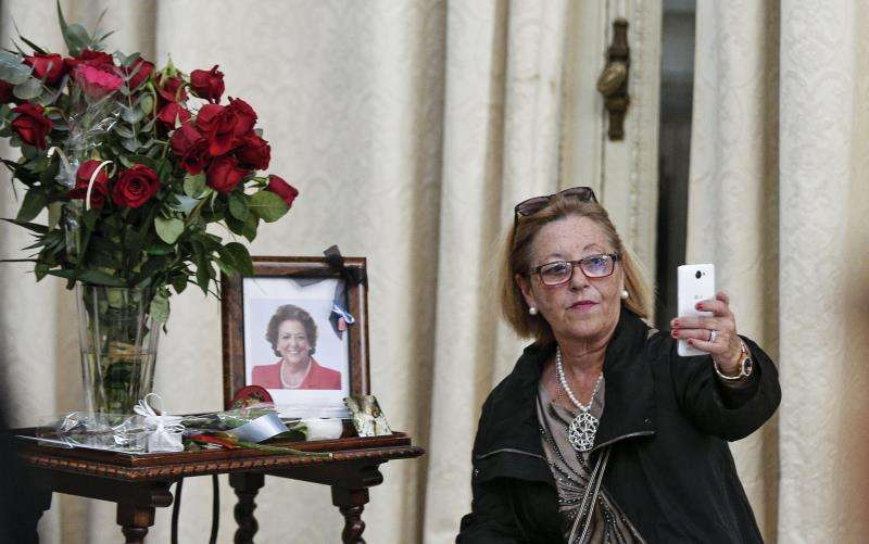 Una mujer se hace una fotografía ante una foto y unas rosas en el Salón de Cristal del Ayuntamiento de València tras firmar en los libros de condolencias de la exalcaldesa de Valencia Rita Barberá, poco después de su fallecimiento. EFE/Archivo