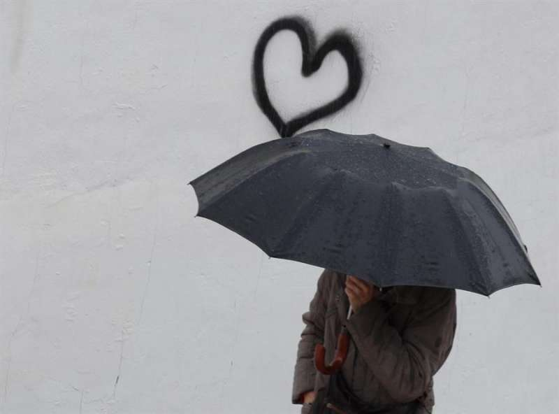 Persona bajo un paraguas / EFE