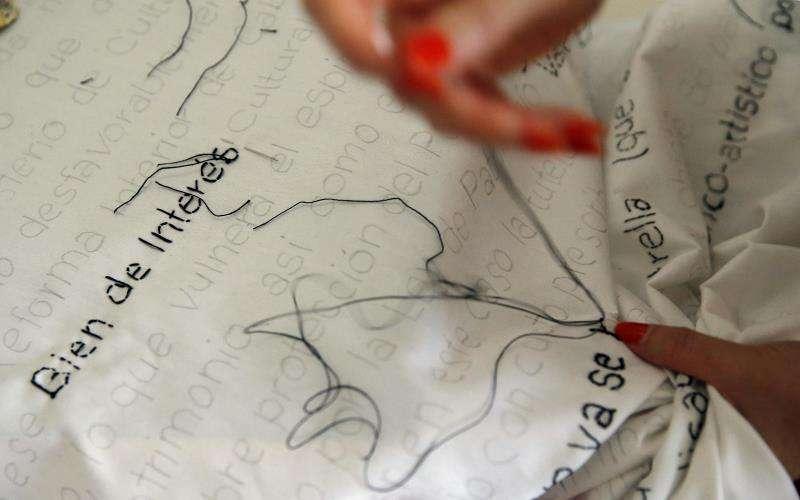 Una vecina del Cabanyal participa en el bordado en tela de las 17 hojas de la orden ministerial de 2009 que dio protección legal al barrio contra los derribos de viviendas. EFE