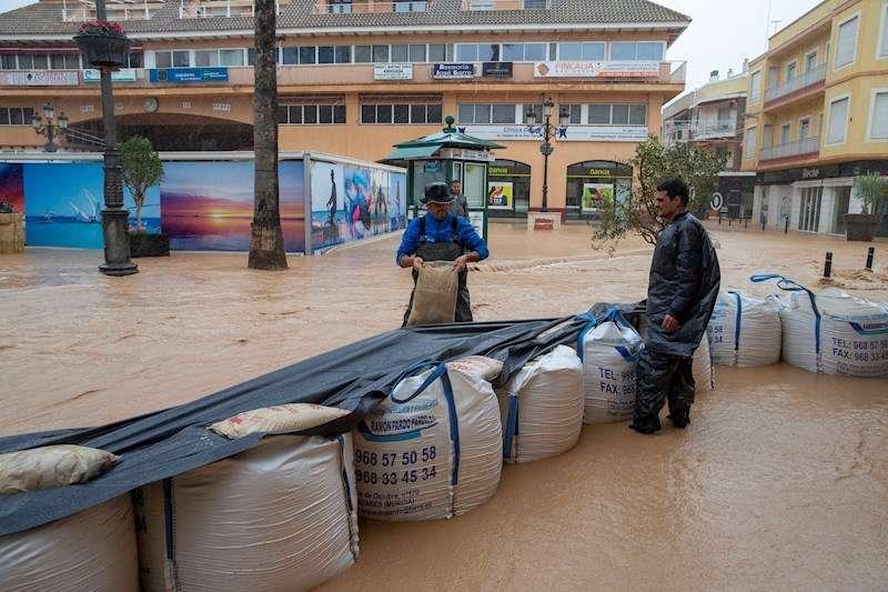 Dos vecinos del municipio de Los Alcázares hacen un dique de contención para evitar que el agua entre en su restaurante. EFE