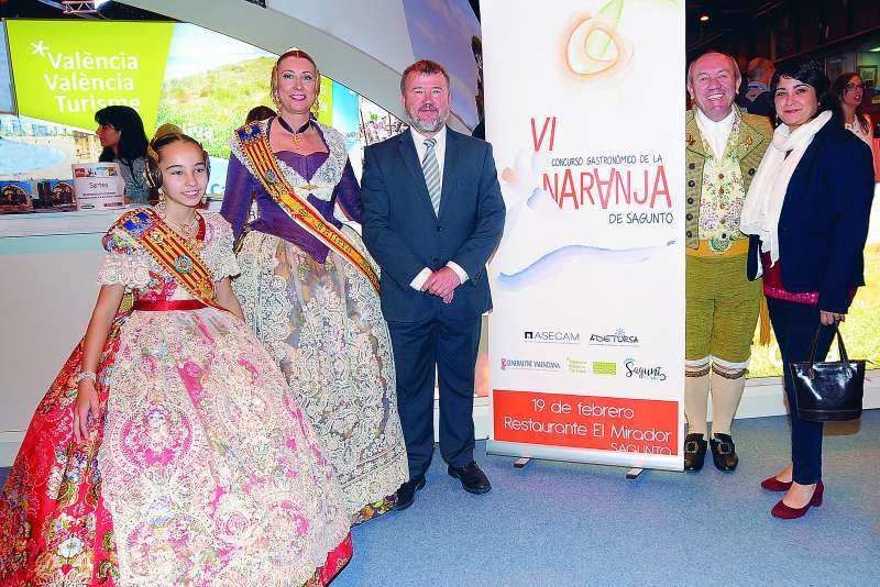 El alcalde y la edila de Turismo de Sagunt posan con las Falleras Mayores y el presidente de la FJFS junto al cartel del concurso en Fitur. EPDA