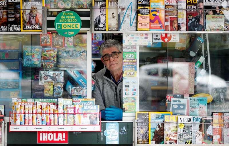 Quiosquero vendiendo periódicos en tiempos del coronavirus. EFE