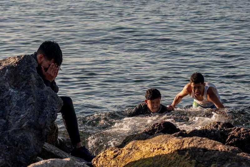 Tres inmigrantes llegan a nado a la playa de El Tarajal, en Ceuta.