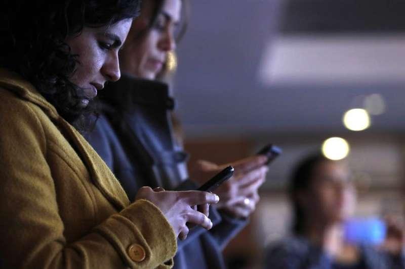 Varias personas consultan sus teléfonos móviles. EFE/Archivo