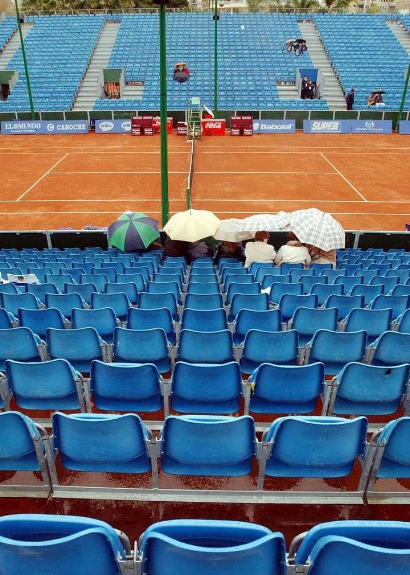 Un grupo de personas se cubre bajo paraguas en la pista central del Club de Tenis Valencia. EFE/Archivo