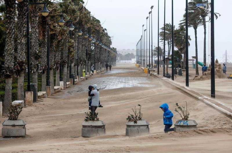 Una mujer cruza el paseo marítimo de Valencia cubierto en parte por la arena que arrastra el fuerte viento. EFE/