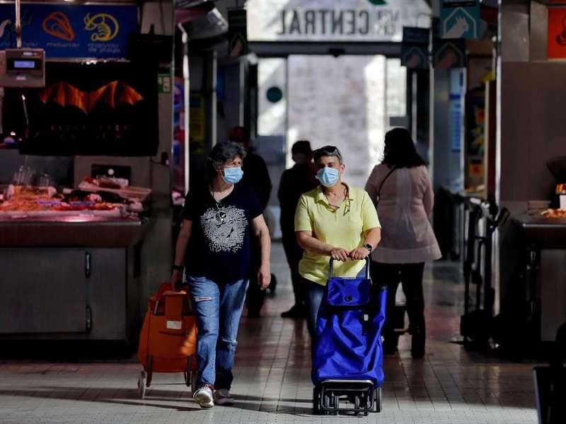 En la imagen, varias personas protegidas con mascarillas en el Mercado Central de València. EFE/Manuel Bruque/Archivo