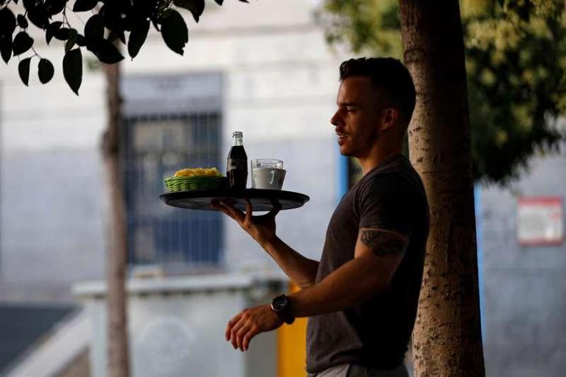 En la imagen, un camarero sirve una mesa en una terraza. EFE/Archivo