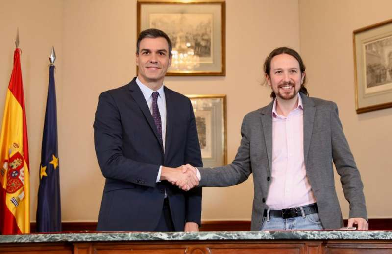 Pedro Sánchez y Pablo Iglesias se dan la mano tras el acuerdo para formar gobierno.