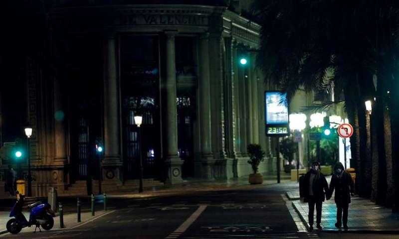 Dos personas caminan por la céntrica calle Barcas de Valencia pocos minutos antes de la medianoche, momento en el que entra en vigor el toque de queda. EFE/Manuel Bruque