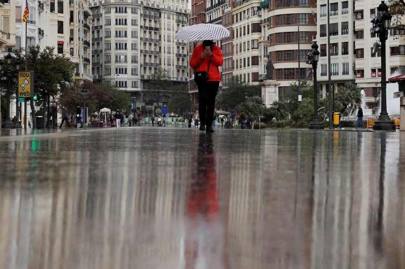Imagen de archivo de una persona que se protege de la lluvia con un paraguas.