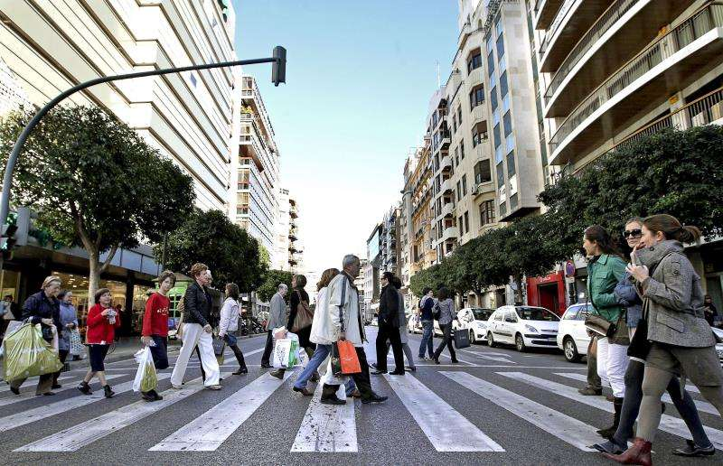 Numerosas personas cruzan la céntrica calle Colón, en València, muy cerca de la sede de RNE. EFE/Archivo