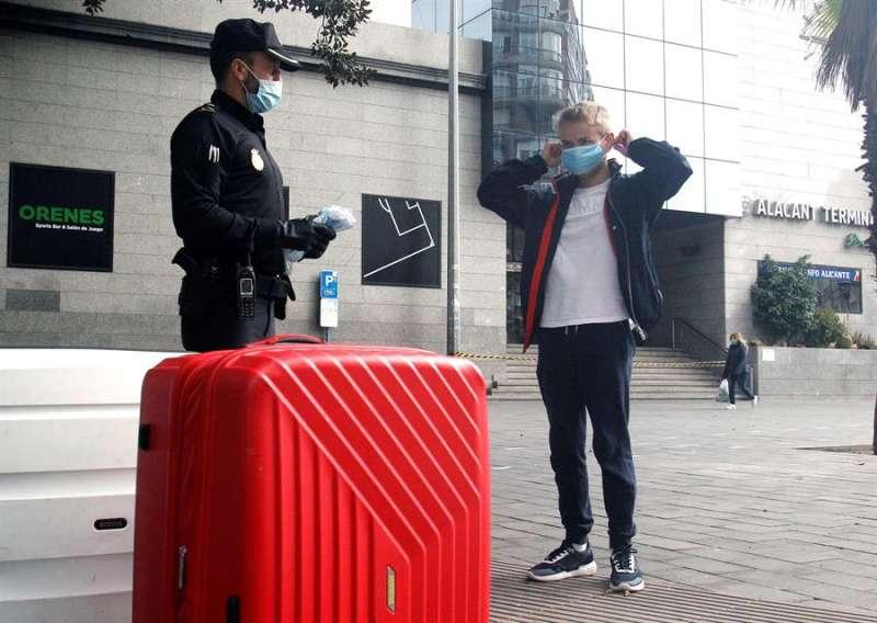 Un policía se dirige a un joven con mascarilla en Alicante. EFE
