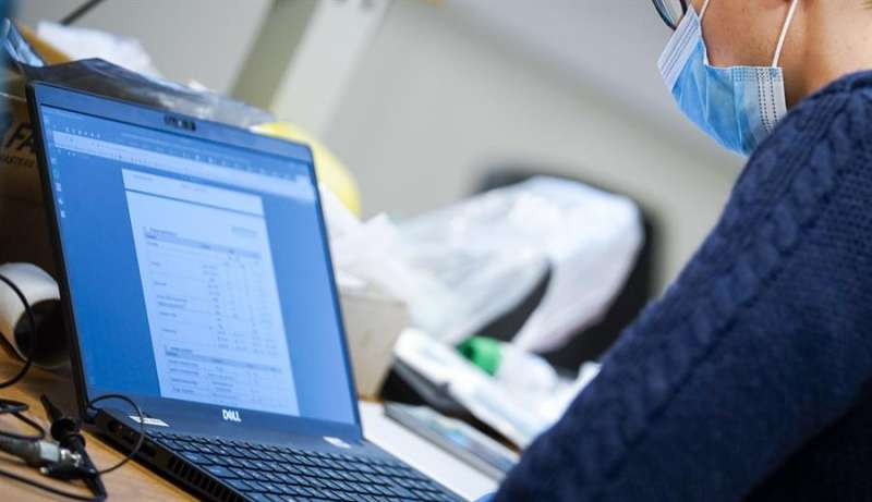 Una persona con mascarilla ante un ordenador. EFE/Archivo