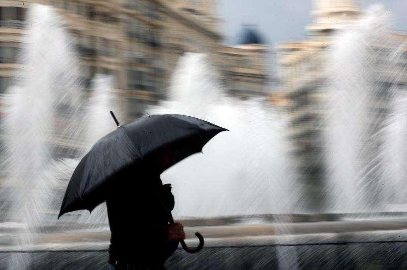 Una persona se resguarda con un paraguas en el centro de València en una imagen de archivo. EFE/Kai Fosterling