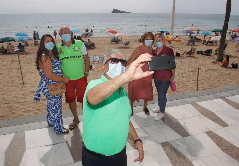 Un grupo de turistas pasean y se toman fotografías en la playa de Levante de Benidorm. EFE/MORELL/Archivo