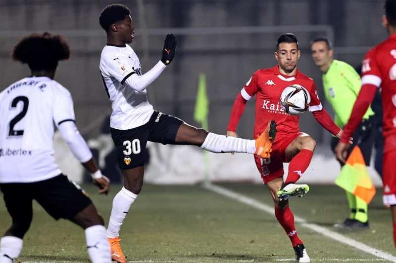 El centrocampista inglés del Valencia Yunus Musah (c) disputa el balón ante el jugador del Alcorcón Carlos Bellvis