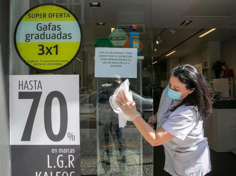 Una mujer con mascarilla limpia los cristales de una óptica. EFE/Archivo