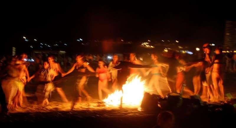 Un grupo de personas baila alrededor de una hoguera en la playa de San Juan de Alicante. EFE