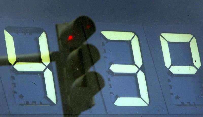 Un semáforo en rojo se refleja en un termómetro de la ciudad de Valencia que marca 43 grados.EFE/Archivo