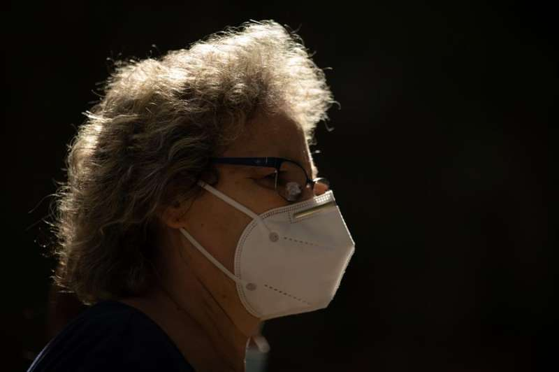Una mujer camina por una calle con mascarilla. EFE/Enric Fontcuberta/Archivo