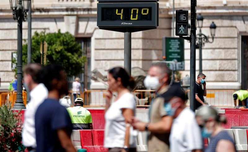 Varias personas pasan ante un termómetro urbano que marca una temperatura de 40º. EFE/Manuel Bruque/Archivo