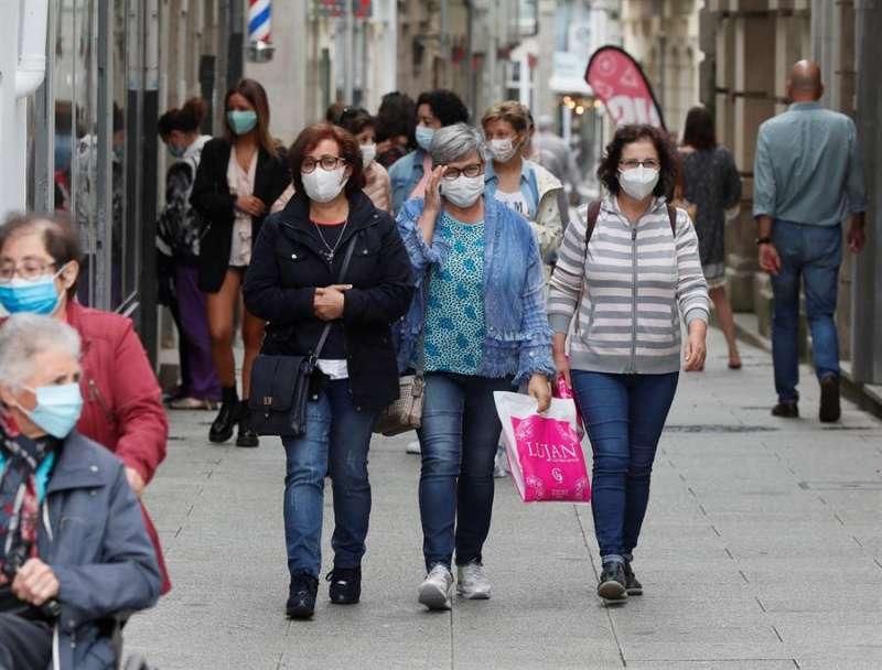 Varias personas caminan con mascarilla por las calles. EFE