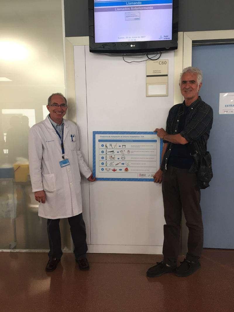 El doctor Pedro Rollán y el ilustrador Miguel Gallardo colocando uno de los paneles en el Hospital de Manises. EPDA