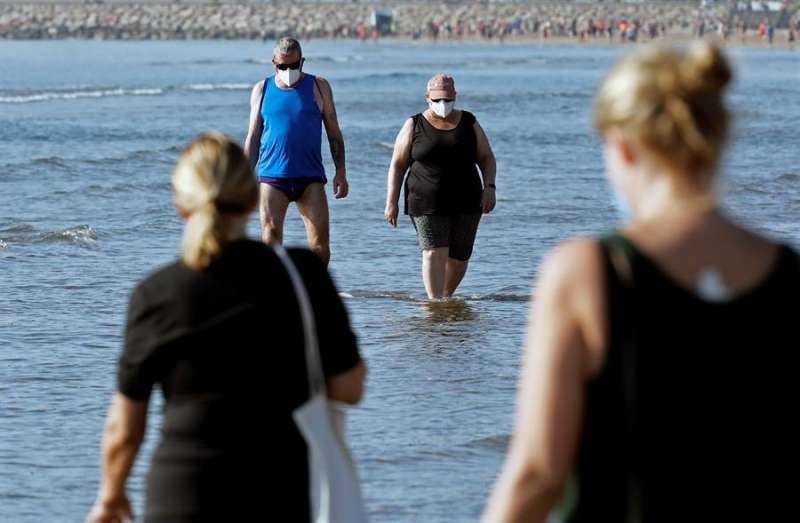 Una pareja protegidas con mascarillas hoy,l sexagésimo octavo día del estado de alarma, en la playa de la Malvarrosa de Valencia.EFE