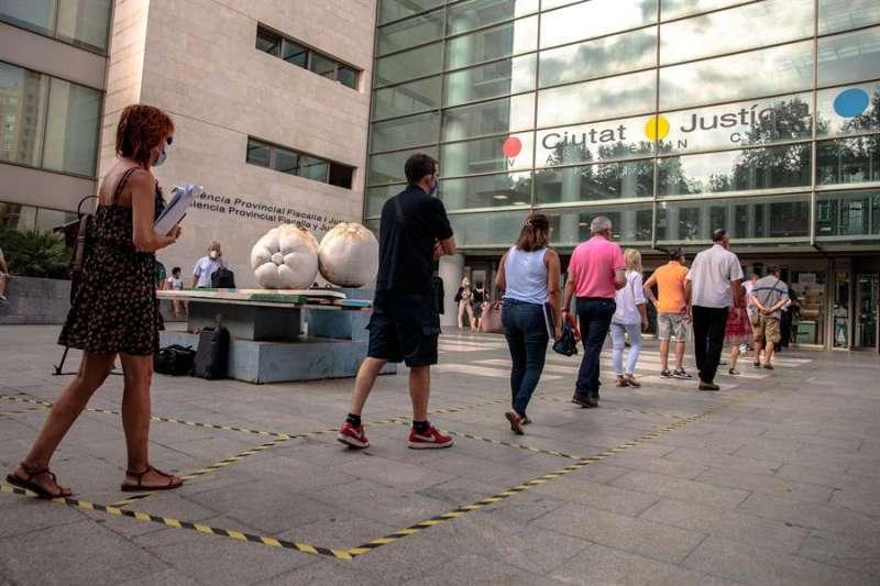 Varias personas hacen cola manteniendo la distancia de seguridad con motivo de la pandemia de la covid para acceder a la Ciudad de la Justicia de València. EFE/ Biel Aliño/Archivo