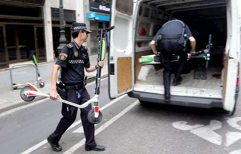 Dos agentes de la Policía Local trabajan en la retirada de unos patinetes de la empresa Lime en septiembre de 2018. EFE
