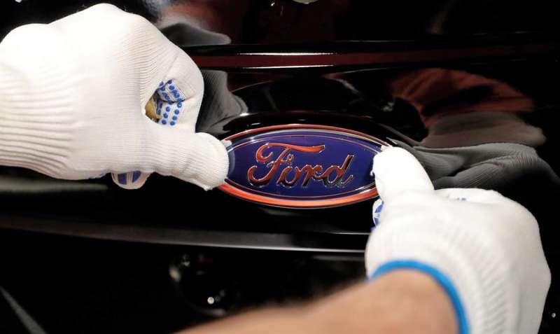 Fotografía de un empleado del fabricante de automóviles Ford mientras coloca el logotipo de la empresa en un vehículo. EFE/ Friedemann Vogel/Archivo