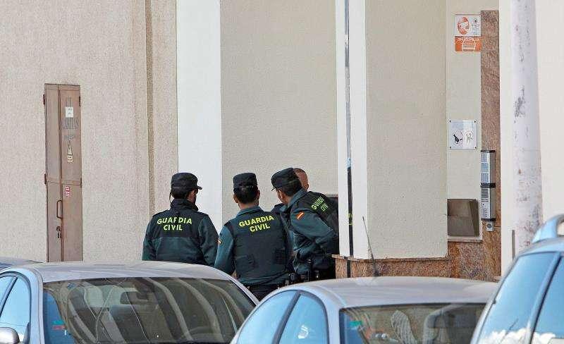 En la imagen, varios agentes de la Guardia Civil a las puertas del edificio donde se halló el cadáver. EFE