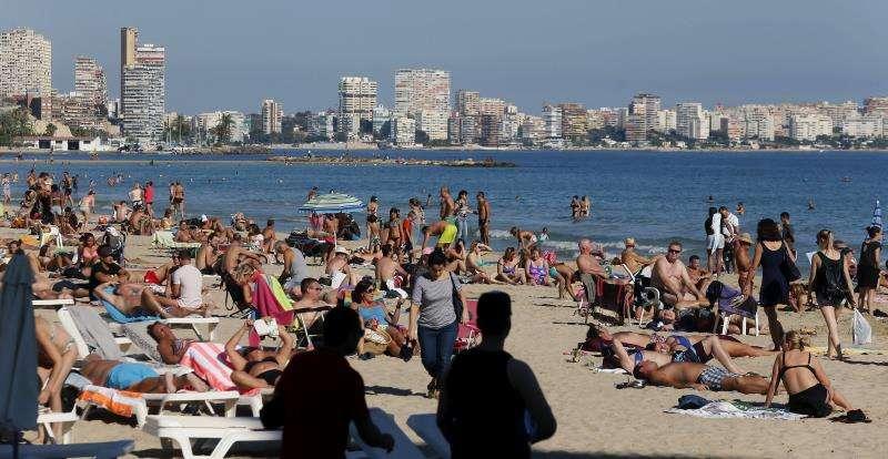 Turistas al sol en la playa del Postiguet en Alicante. EFE/Archivo