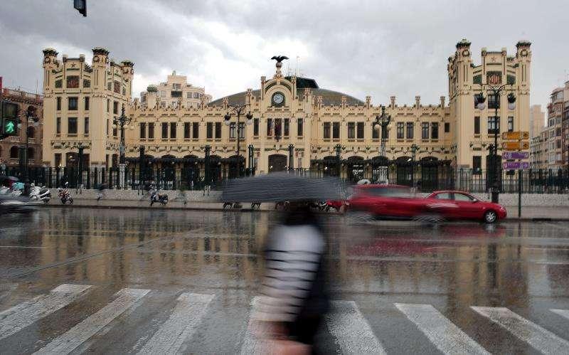 Una mujer se protege de la lluvia esta mañana en el centro de València. EFE/Archivo