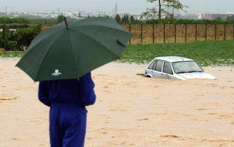 Rescatada una mujer en Vila-real atrapada en su coche en una zona inundada. Un hombre observa un coche sumergido en el agua tras un episodio de lluvias torrenciales en las inmediaciones de una localidad valenciana. EFE/Archivo