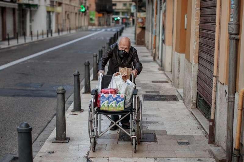 Una persona mayor protegida con una mascarilla transporta productos de la compra en una silla de ruedas, en una imagen de este miércoles. EFE/Biel Aliño