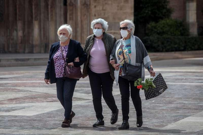 Tres señoras caminan cogidas del brazo en una céntrica plaza de València. EFE