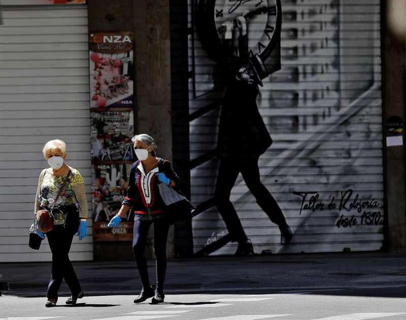 Dos mujeres con mascarilla caminan por una céntrica calle de València. EFE/Manuel Bruque/Archivo