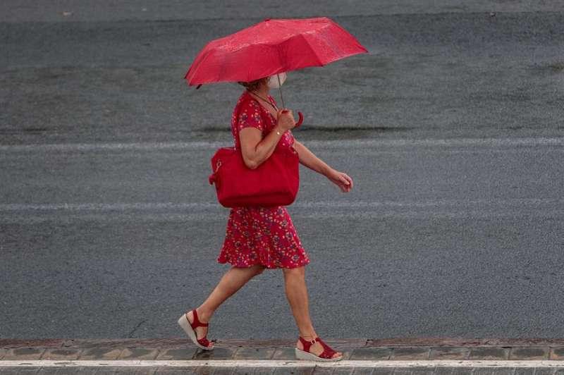 Una mujer camina bajo la lluvia, en agosto en València. EFE