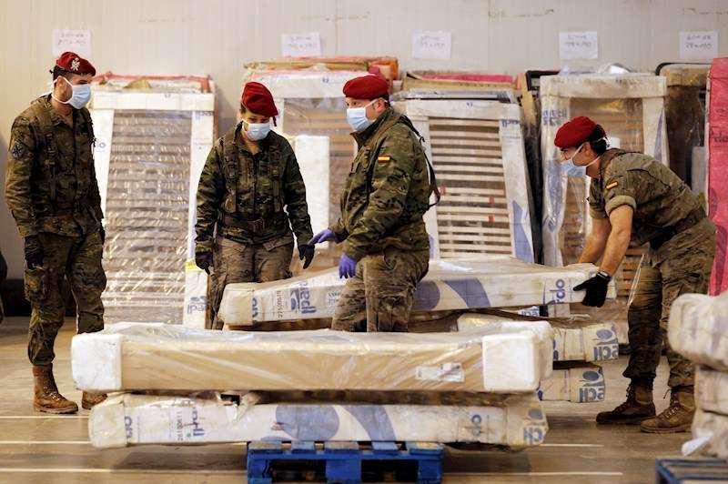 Varios soldados trabajan en el traslado y almacenamiento de 386 camas geriátricas para proceder a su posterior distribución. EFE