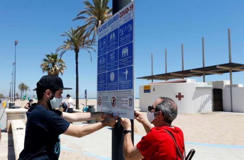 Dos operarios colocan un cartel en la playa de la Malvarrosa donde han empezado las labores de señalización. EFE
