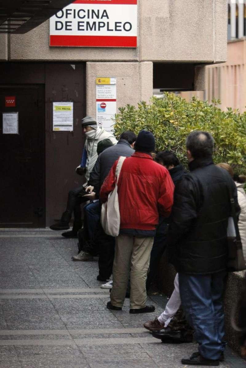 Varias personas esperan en la cola a la entrada de una Oficina de Empleo. EFE/Archivo