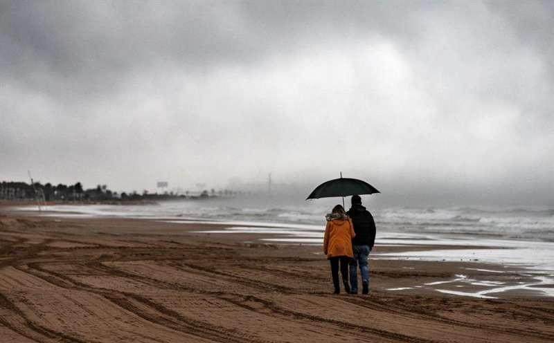 En la imagen, una pareja pasea por la playa de la Malvarrosa de València en un día lluvioso. EFE/ Manuel Bruque/Archivo